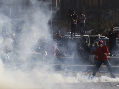 A protester prepares to pick up a tear gas canister, earlier thrown by riot police, during clashes along a road leading to the U.S. embassy, near Tahrir Square in Cairo September 14, 2012. (Reuters/Amr Abdallah Dalsh)