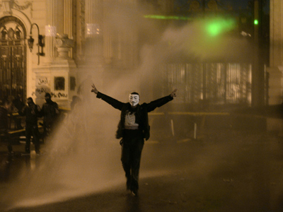 A protestor wearing a Guy Fawkes mask, trademark of the anonymous movement and based on a character in the film V for Vendetta, is sprayed by water as Egyptian security use water cannons to disperse anti-government protestors as they throw stones into the grounds of the al-Kobaa Presidential palace in Cairo, on February 15, 2013 (AFP Photo / Mohammed El-Shahed)