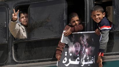 "Palestinian boys hold a poster of children reading ""Rescue Gaza"" as another flashes the victory sign near the southern Gaza Strip's Rafah border crossing with Egypt (AFP Photo / Said Khatib)"