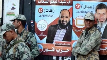Egyptian soldiers stand in front of campaign posters for candidates from the hardline Islamist Salafist Al-Nur Party, in the coastal city of Alexandria on December 5, 2011 (AFP Photo / Str)