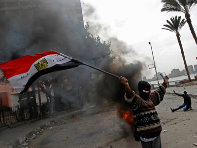 An Egyptian protester waves his national flag as he gestures towards riot police during clashes near Cairo's Tahrir Square on January 28, 2013 (AFP Photo / Mohammed Abed)