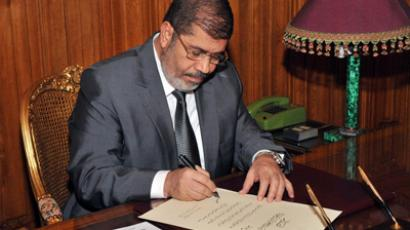 A hand out picture released by Egyptian Presidency shows Egyptian President Mohamed Morsi at his office in the presidential palace in Cairo on December 26, 2012, as he signs into law a new constitution voted in despite weeks of opposition protests (AFP Photo)