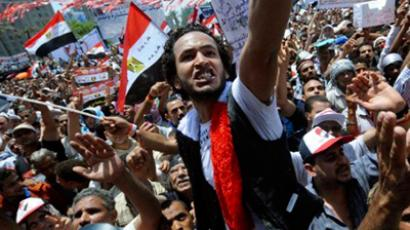 Egyptian protesters wave their national flag and shout slogans as thousands crowd Cairo's landmark Tahrir Square on July 15, 2011 to demand political change as anger grows with the military rulers over the slow pace of reform (AFP Photo / Mohamed Hossam)