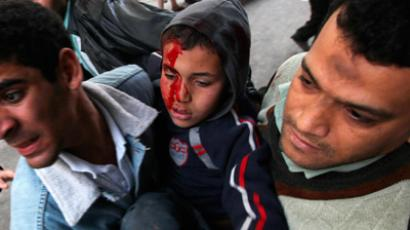 An injured boy receives help from protesters during clashes with riot police near cabinet offices near Tahrir Square in Cairo December 18, 2011 (Reuters / Amr Abdallah Dals)