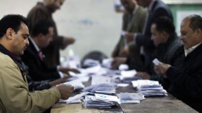 Polling station officials deposit ballots during the second round of a referendum on a new draft constitution in Giza, south of Cairo, on December 22, 2012 (AFP Photo)