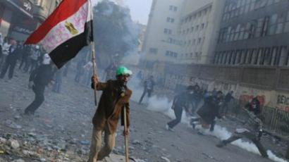 Cairo : An Egyptian man walks with a stick and holds up a national flag as demonstrators dodge tear gas during clashes in a Cairo street. (AFP Photo/Mohammed Hossam)