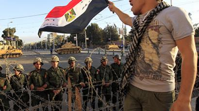 A protester against Egypt's President Mohamed Mursi waves an Egyptian flag in front of Republican Guard soldiers standing behind a barbed wire barricade guarding the presidential palace in Cairo. (Reuters / Mohamed Abd El Ghany)