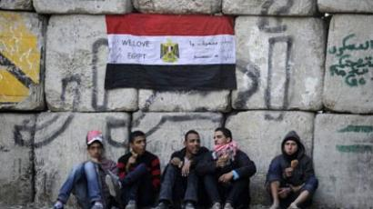 Egyptian protesters sit in front of the barricades erected by the Egyptian army, near the government cabinet offices off Tahrir Square in central Cairo on December 21, 2011 (AFP Photo / FILIPPO MONTEFORTE)