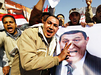 Pro-government Egyptian protesters carry a banner bearing a photo of Egyptian President Hosni Mubarak during a march near Tahrir square in central Cairo February 2, 2011
