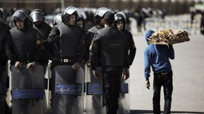 Cairo: A vendor walks past Egyptian riot policemen standing guard outside a court in Cairo on February 22, 2012 (AFP Photo/Marco Longari)
