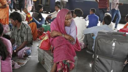 Passengers sit on a platform for their train to arrive as they wait for electricity to be restored at a railway station in New Delhi July 31, 2012 (Reuters/Adnan Abidi)