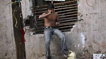 An Indian ragpicker brushes his teeth as he begins his morning routine at a ragpickers colony in New Delhi on May 31, 2010 (AFP Photo / Tengku Bahar)