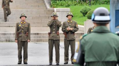 North Korean soldiers look towards South side as a South Korean soldier (R) stands guard while Army General James Thurman (not pictured), new commander of US forces in South Korea, visits to the truce village of Panmunjom in the demilitarized zone dividing the two Koreas on July 15, 2011 (AFP Photo / Pool / Jung Yeon-Je)