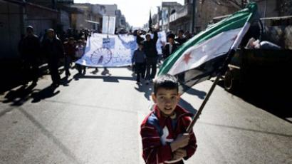 A young boy carries the Syrian-rebel adopted flag during an anti-regime demonstration in the Syrian village of al-Qsair, 25 km southwest of the flashpoint city Homs, on February 3, 2012 (AFP Photo / Alessio Romenzi)