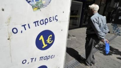 Greece, Athens: A man walks in a shopping area in central Athens by an 'everything for 1 euro' sign on May 24, 2011. (AFP Photo / Louisa Gouliamaki)