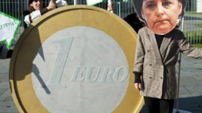 A protester dressed as German Chancellor Angela Merkel stands next to a giant 1 Euro coin during a demonstration in front of the chancellery in Berlin October 21, 2011 (AFP Photo / John Macdougall)