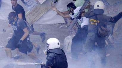 Riot policemen spray tear gas as they clash with demonstrators in front of the Greek parliament on June 29, 2011 during a protest part of the 48-hour general strike against the bankruptcy-threatened government which is desperately trying to push through sweeping austerity cuts (AFP Photo / Angelos Tzortzinis)