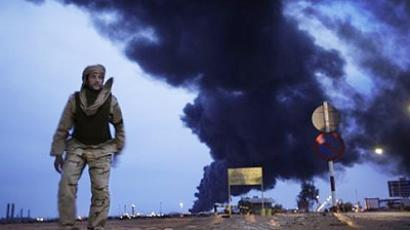 In this photo taken during a government-organised visit for foreign media, a  fighter puts his shoes on after making his evening prayers in the desert as a plume of smoke rises from the burning oil refinery in Ras Lanouf, 380 miles (615 kilometers) southeast of the capital Tripoli, in Libya