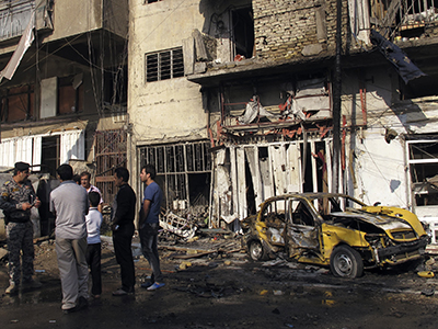 Residents gather at the site of a car bomb attack in Karrada district in Baghdad November 14, 2012. (Reuters / Mohammed Ameen)