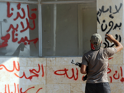 A member of Jihadist group Shura Taliban Islam writing an Arabaic slogan (No Islam without Jihad) with spray on the wall of the Bab al-Hawa border gate on July 21, 2012 (AFP Photo / Bulent Klic)