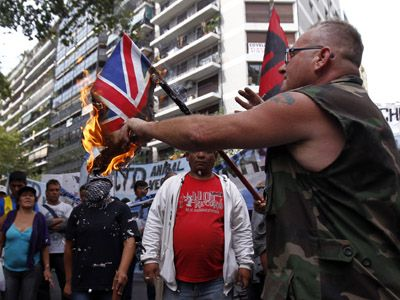 An Argentine Falklands War veteran burns a Union Jack flag during a demonstration outside the British embassy in Buenos Aires April 2, 2012 (Reuters / Marcos Brindicci)