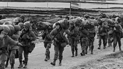 Argentine soldiers are seen 13 April 1982 in their way to occupy the captured Royal Marines base in Puerto Argentino/Port Stanley, a few days after the Argentine military dictatorship seized the islands Malvinas/Falklands, starting a war between the Argentina and the United Kingdom. (AFP Photo / Daniel Garcia)