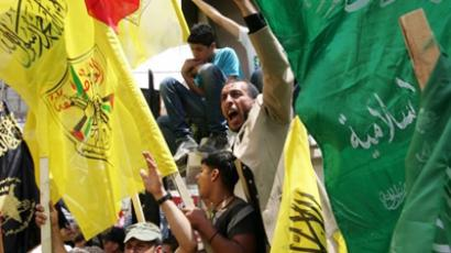 Palestinian supporters of Hamas Islamist movement and of Fatah party waving their faction's flags during a rally to support the Palestinian political unity deal, in the West Bank city of Jenin, on May 12, 2011 (AFP Photo / Saif Dahlah)
