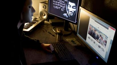 A masked hacker, part of the Anonymous group, hacks a website (AFP Photo / Jean-Philippe Ksiazek)