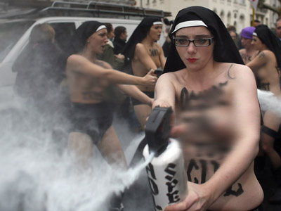 Topless activists of the Ukrainian women movement Femen use sprays during a protest against the fierce opposition from the Roman Catholic Church to authorise gay marriage on November 18, 2012 in Paris. (AFP Photo/Kenzo Tribouillard)