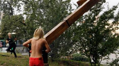Activists of the Ukrainian feminist group Femen use a chainsaw to cut down an Orthodox cross, erected to the memory of victims of the political repression in Kiev (Reuters/Anatolii Stepanov)