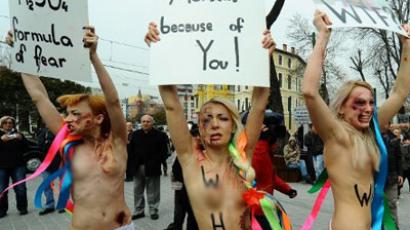 Ukrainian Femen activists with fake injuries hold placards as they protest against domestic violence in front of the Hagia Sofia in Istanbul on March 8, 2012 during the International Women's Day (AFP Photo / Mustafa Ozer; FEMEN video from vimeo.com)