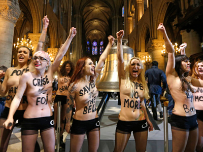 Activists from the women's rights organisation Femen protest in front of the new eight bronze bells displayed in the nave of Notre-Dame de Paris Cathedral in Paris February 12, 2013  (Reuters / Charles Platiau)