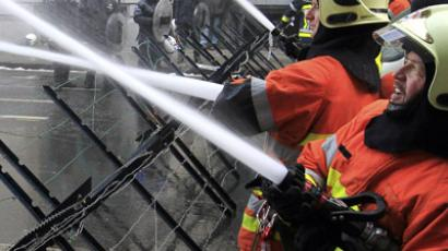 Firemen spray water outside a cabinet meeting during a demonstration in Brussels. (Reuters / Yves Herman)