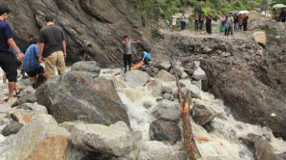 In this handout photograph received from the Sikkim Information and Public Relation Department (IPR) and taken on September 23, 2012 onlookers watch as rescue work following landslides caused by flash floods takes place on the Mongon – Chungthang road, some 30 kms north of the Gangtok, capital of Sikkim (AFP Photo / Sikkim IPR Dept)