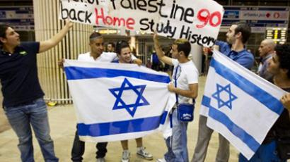 "Israeli youth from France hold Israeli flags and an anti-Palestinian banner at Ben Gurion Airport on July 8, 2011 as they protest against the ""Pro-Palestinian Fly-In"" organised by European and North American activists to travel en masse to the West Bank (AFP Photo / Jack Guez)"