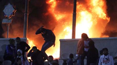 A soccer fan flees from a fire at Cairo stadium February, 1, 2012 (Reuters / Stringer)