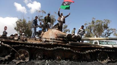 Libyan rebels waving their flag on top of a wrecked tank belonging to Gaddafi's forces on the western entrance of Benghazi on March 20, 2011 (AFP Photo / Patrick Baz)