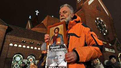 "Minsk: A man holds an icon and a poster depicting Mikola Statkevich, a presidential candidate, who was jailed after the last December controversial vote, reading ""Free Statkevich!"" during a solidarity action near a Catholic cathedral in Minsk, late on January 19, 2011, marking a month anniversary of the event. (AFP Photo / Viktor Drachev)"