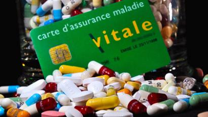 """Carte vitale"", French health insurance card set next to a jar containing drug capsules and pills. (AFP Photo/Philippe Huguen)"