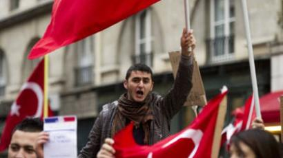People holding the Turkish flag take part in a rally next to the French National Assembly on December 22, 2011 in Paris as the French parliament is today expected to approve the bill, which would see anyone in France who publicly denies the 1915 Armenian genocide face a year in jail and a fine of 45,000 euros ($58,000) today and is expected to approve it (AFP Photo / Fred Dufour)