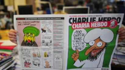 A person reads on November 1, 2011 in Paris an issue of Satirical French newspaper Charlie Hebdo to be published on November 2, 2011 (AFP Photo / MARTIN BUREAU)