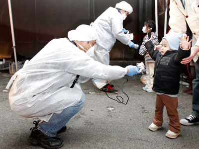 Officials in protective gear check for signs of radiation on children who are from the evacuation area near the Fukushima Daini nuclear plant in Koriyama, March 13, 2011.(Reuters / Kim Kyung-Hoon)