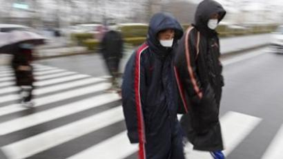 People walk to a center to scan residents, who have been within 20 kilometers of the Fukushima Dai-ichi nuclear plant damaged by Friday's earthquake, in the rain Tuesday, March 15, 2011, in Koriyama, Fukushima Prefecture, Japan