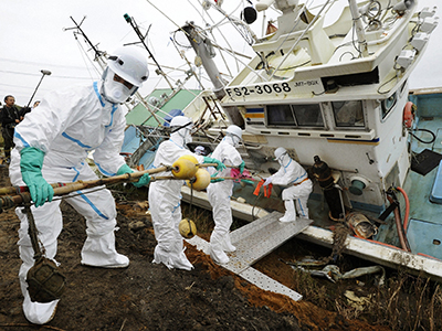 Volunteers to remove radioactive substances from a fishing boat in Minamisoma, Fukushima Prefecture, in this photo taken by Kyodo October 24, 2011. (Reuters / Kyodo)