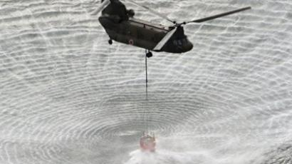Japan's Self-Defense Forces's helicopter scooping water off Japan's northeast coast on its way to the Fukushima Dai-ichi nuclear power plant in Okumamachi Thursday morning, March 17, 2011