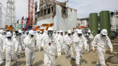Members of the media and Tokyo Electric Power Co. (Tepco) employees look at the No. 4 reactor building (rear), amongst tsunamai damage, at the company's Fukushima Dai-Ichi nuclear power plant in Okuma Town, Fukushima Prefecture. (AFP Photo / Tomohiro Ohsumi)