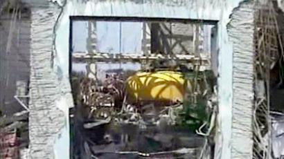 This handout picture taken by Tokyo Electric Power Co (TEPCO) on April 15, 2011 and released on April 17, shows a video image, taken by T-Hawk remote controled drone of the Tokyo Electric Power Co (TEPCO) showing the top part of the nuclear reactor containment vessel (yellow) at the fourth reactor building (AFP Photo / HO / TEPCO)