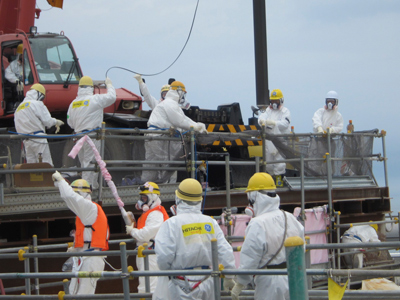 Workers wearing protective suits, work for removing unused nuclear fuel assemblies stored in the spent fuel pool of TEPCO's tsunami-crippled Fukushima Daiichi Nuclear Power Plant No. 4 reactor building in Fukushima prefecture (Reuters / Tokyo Electric Power Co / Handout)