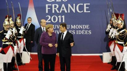 French President Nicolas Sarkozy (R) welcomes German Chancellor Angela Merkel (C) in front of French Foreign Minister Alain Juppe prior to holding crisis talks with EU and IMF representatives in Cannes, southeastern France, on November 2, 2011 on the eve of the G20 Summit of Heads of State and Government (AFP Photo / LIONEL BONAVENTURE)