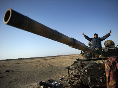 Libya, Ajdabiya: A rebel fighter sits on a destoryed tank on the entrance to the city of Ajdabiya on April 5, 2011. (AFP Photo / Odd Andersen)